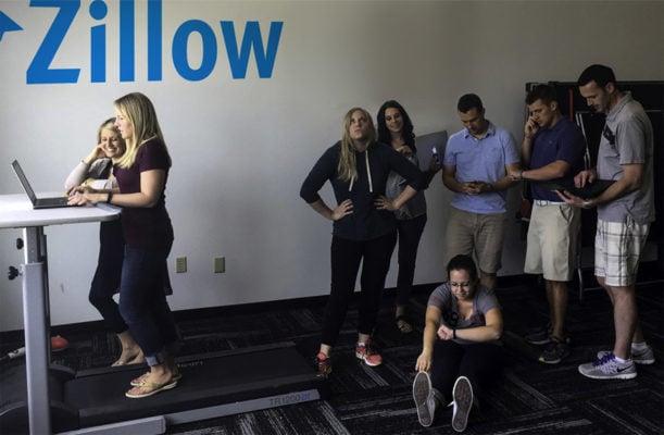 Chez Zillow, des personnes attendent derrière un TMD alors que deux collaboratrices sont en train de travailler dessus.